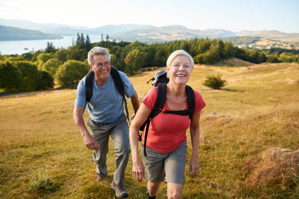 portrait of senior couple climbing hill on hike through countryside in lake district uk together - hiking stock photos and pictures