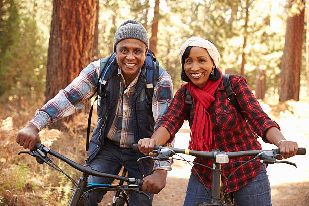 Portrait Of Senior Couple Cycling In Fall Woodland stock photo