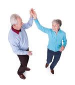 Portrait Of Senior Couple Dancing On White Background