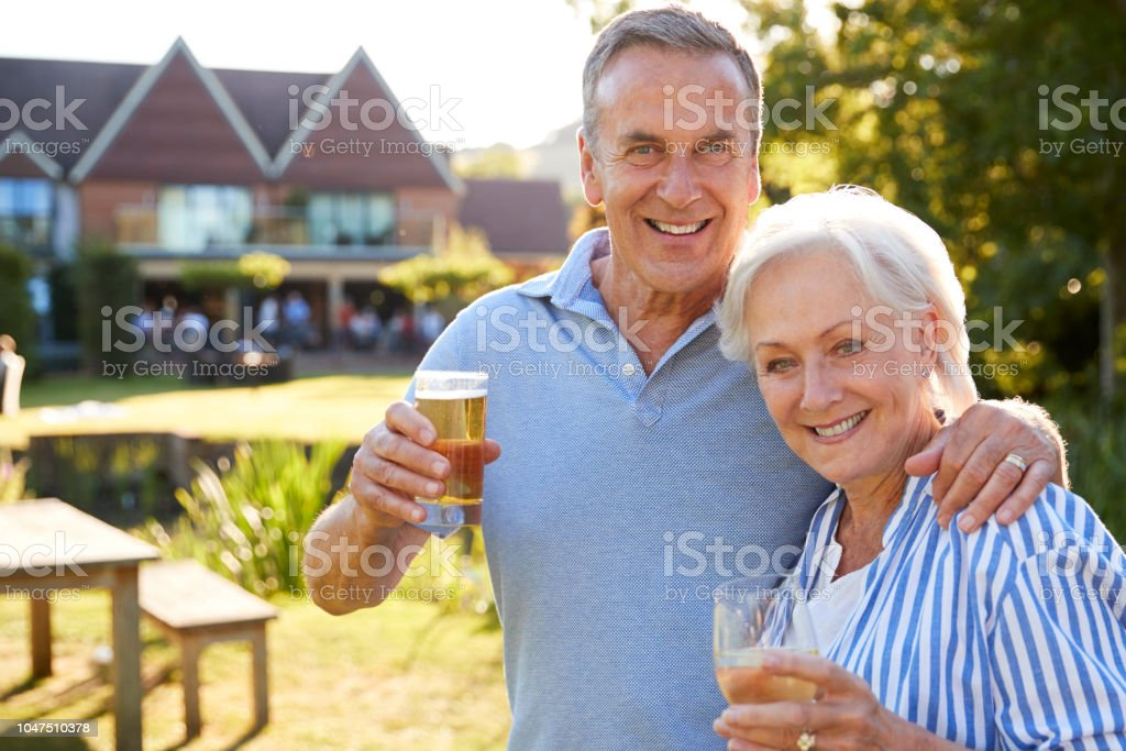 Portrait Of Senior Couple Enjoying Outdoor Summer Drink At Pub стоковое фото