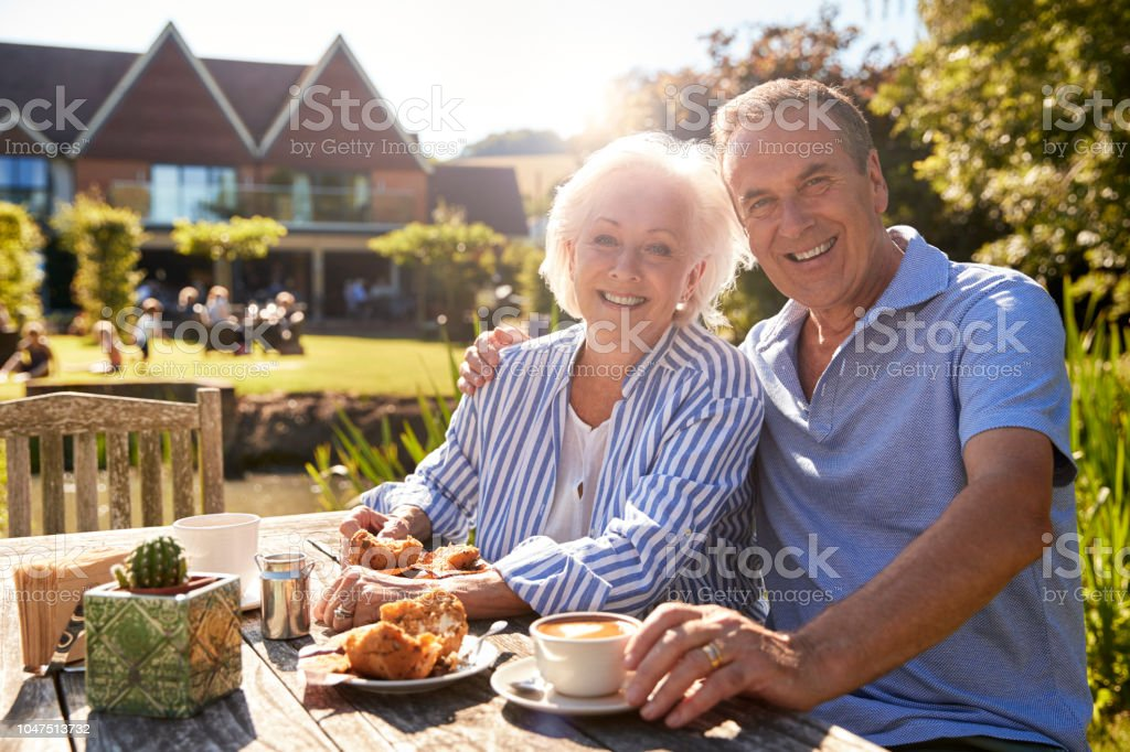 Portrait Of Senior Couple Enjoying Outdoor Summer Snack At Cafe стоковое фото