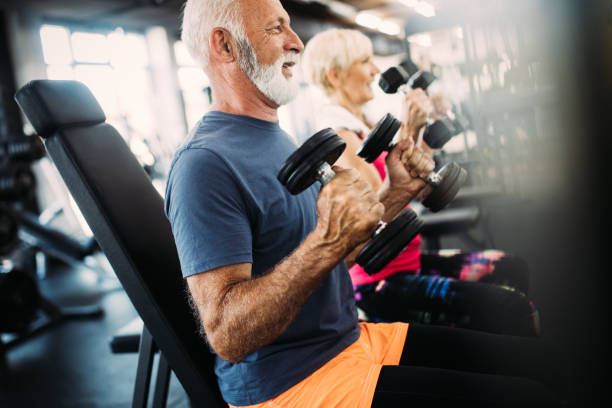 portrait of senior couple exercising in gym - active lifestyle stock pictures, royalty-free photos & images