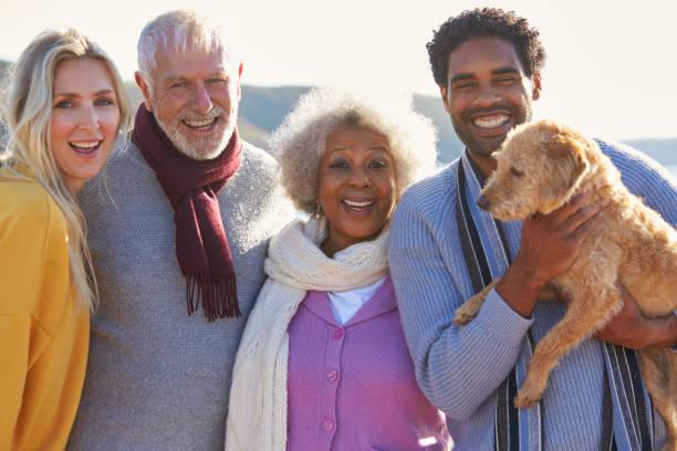 Portrait of senior couple walking along shoreline with adult and dog picture id1203742185?b=1&k=6&m=1203742185&s=612x612&w=0&h=r5uppytqxu xdyc7kcxsslbcub 6foruf 5uu4dyrw0=