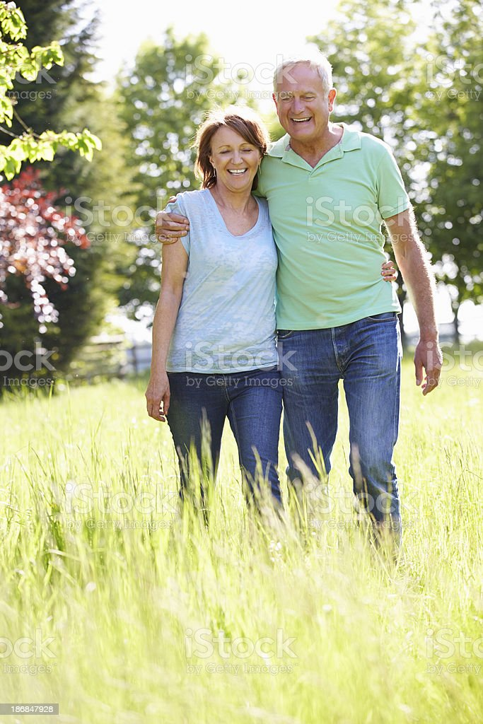 Portrait Of Senior Couple Walking In Summer Countryside royalty-free stock photo