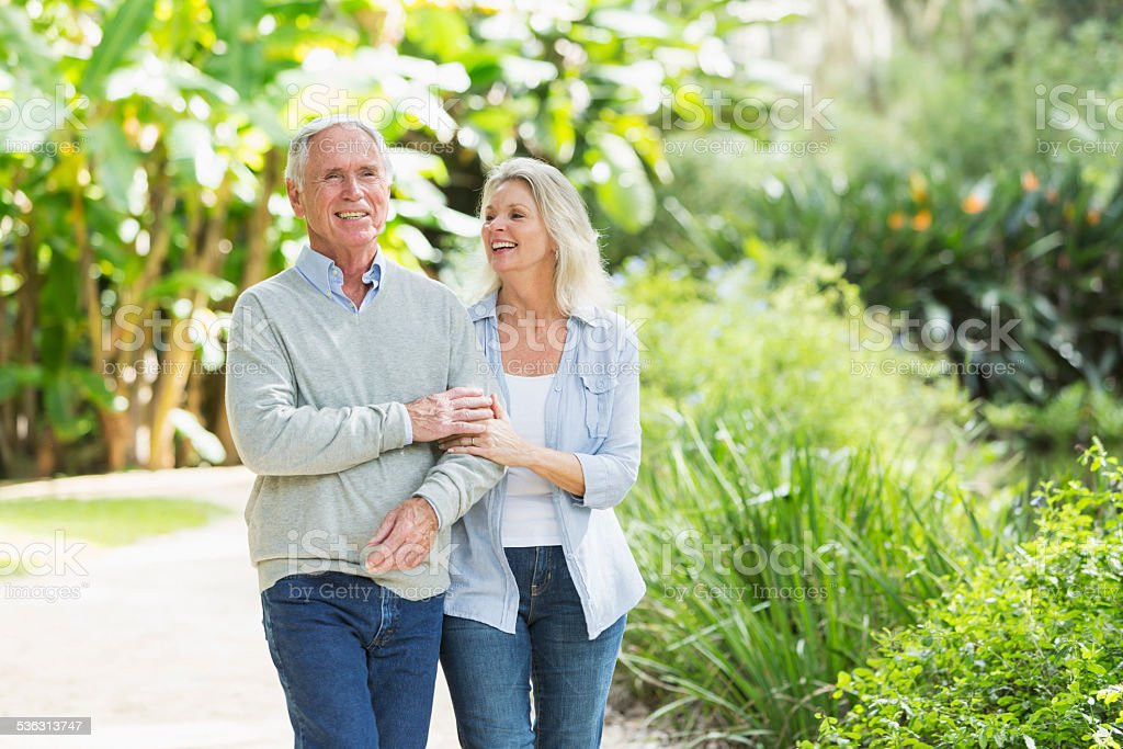 Portrait of senior couple walking in the park stock photo