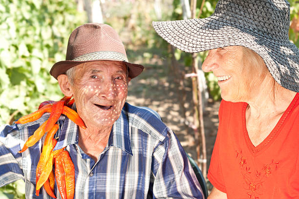 portrait of senior couple with peppers stock photo