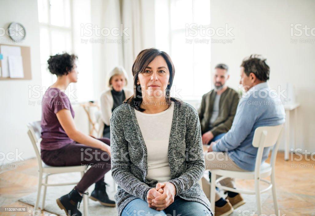 Portrait of senior depressed woman during group therapy. A portrait of senior depressed woman during group therapy. A Helping Hand Stock Photo