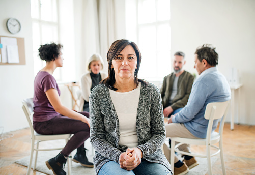 Portrait Of Senior Depressed Woman During Group Therapy Stock Photo - Download Image Now