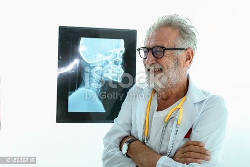840514774istockphoto Portrait of senior doctor in hospital with x-ray film background 1018636216
