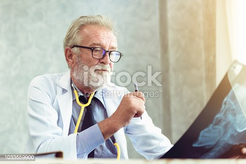 840514774istockphoto Portrait of senior doctor is working and examining X-Ray film for his patient in examination room, Healthcare and occupational concept 1033559900