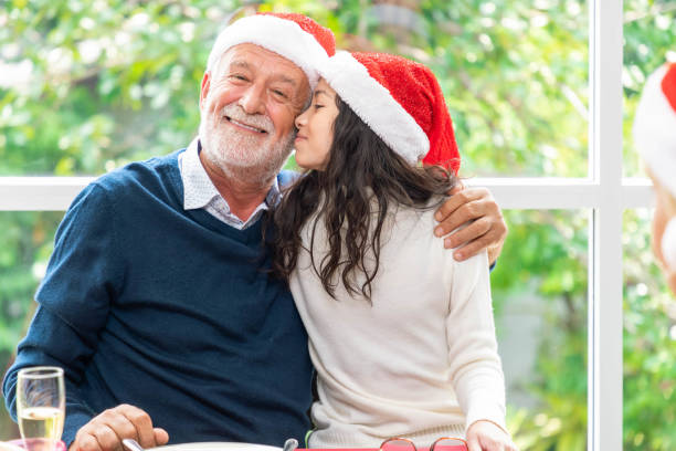 Portrait of senior elderly man grandfather and girl during family dinner party celebrate Christmas holiday festival Portrait of senior elderly man grandfather and girl during family dinner party celebrate Christmas holiday festival little girl kissing dad on cheek stock pictures, royalty-free photos & images