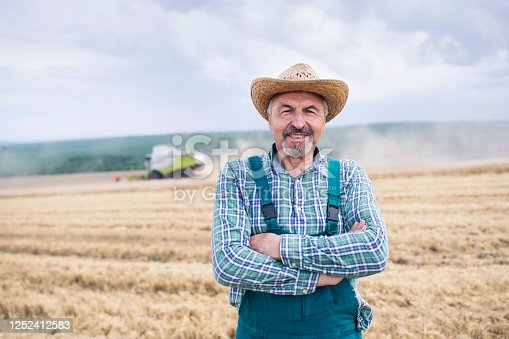 Front view of senior farmer with arms crossed in front of combine harvesting on agriculture field.