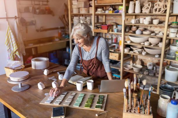 portrait of senior female pottery artist in her art studio - pensionati lavoratori foto e immagini stock