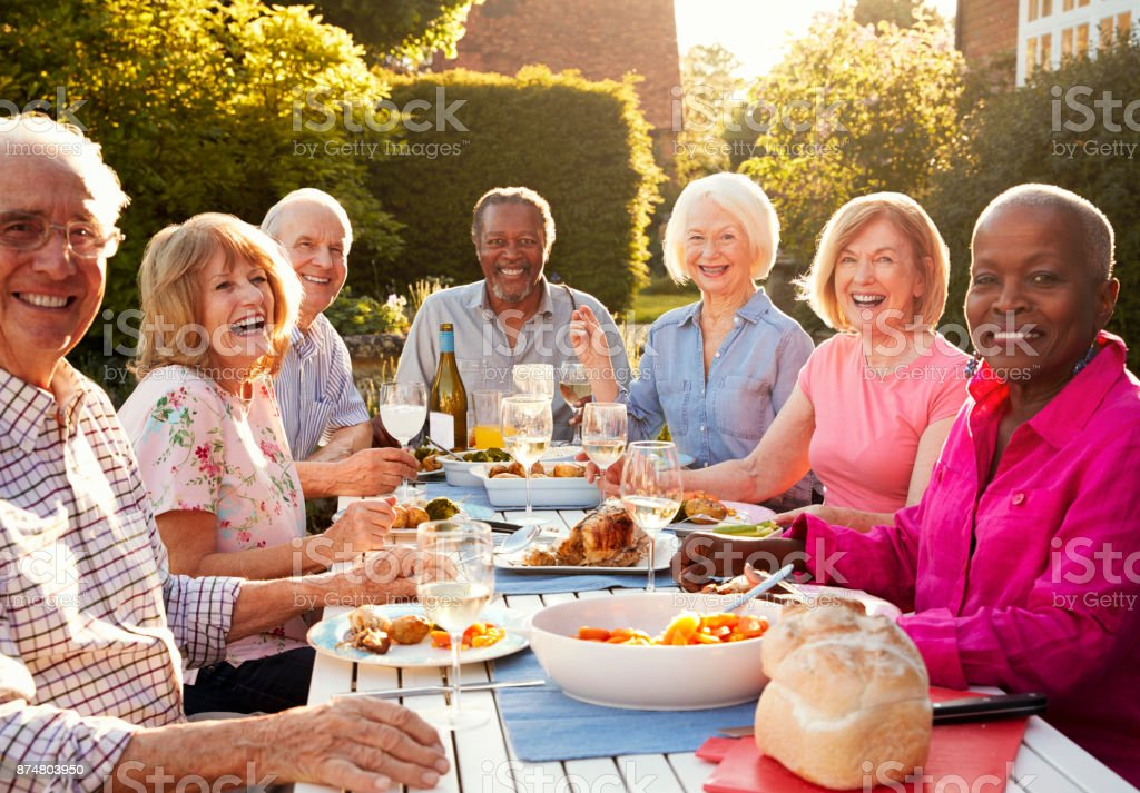 Portrait Of Senior Friends Enjoying Outdoor Dinner Party At Home стоковое фото