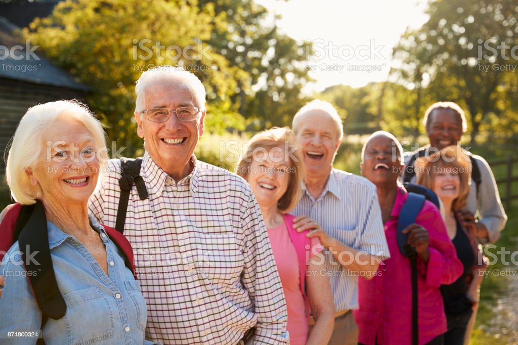 Portrait Of Senior Friends Hiking In Countryside stock photo