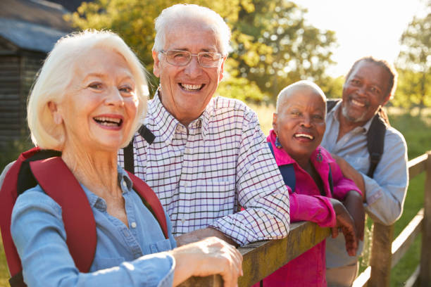 portrait of senior friends hiking in countryside - elderly group stock photos and pictures