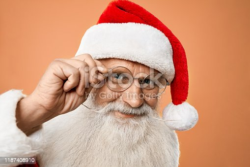 istock Portrait of senior kind Santa Claus holding hand on glasses 1187408910