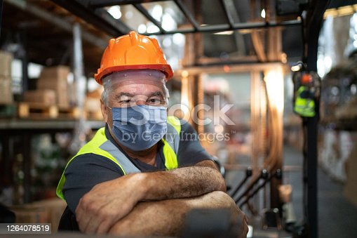 Portrait of senior male worker driving forklift in warehouse