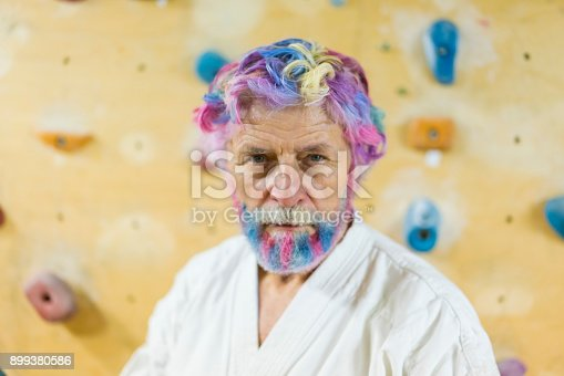 Front view portrait of senior man with rainbow colored hear and beard as rainbow warrior.