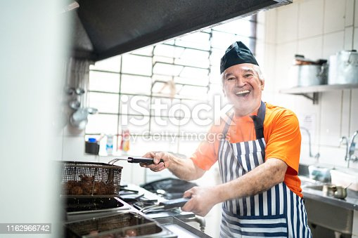 Portrait of senior man cooking at commercial kitchen