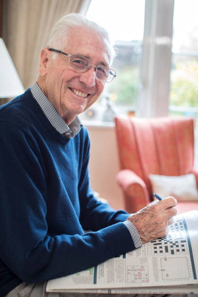 Portrait Of Senior Man Doing Crossword Puzzle At Home stock photo