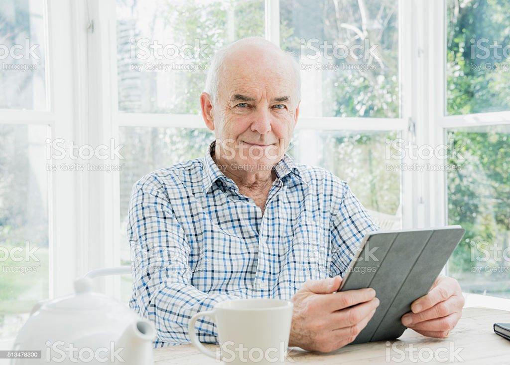 Portrait of senior man holding digital tablet looking at camera stock photo