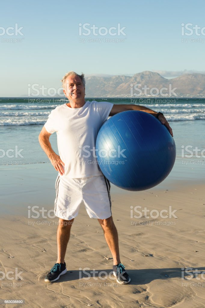 Portrait of senior man holding exercise ball while standing at beach foto de stock royalty-free