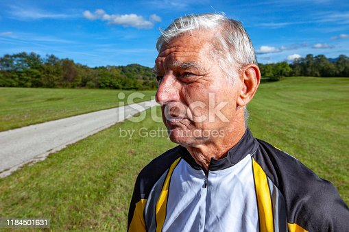 Portrait of Senior Man in Sports Clothing Standing on Meadow By Country Road.