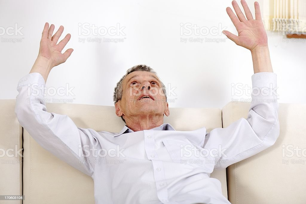 Portrait Of Senior Man On Sofa with hands up royalty-free stock photo