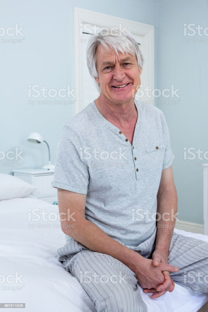 Portrait of senior man sitting on bed at home foto stock royalty-free