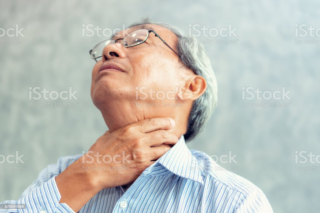 Portrait of senior man touching his neck and having throat irritation stock photo
