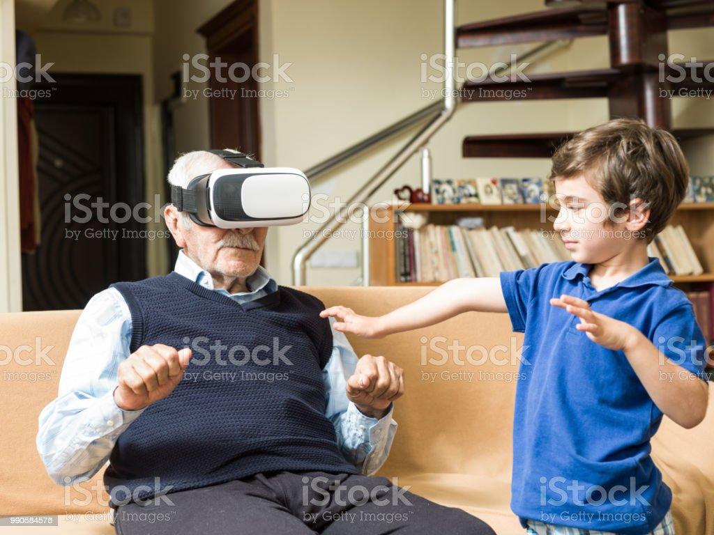 遊び心のある素晴らしい孫と VR のヘッドセットを使用して年配の男性の肖像画 ストックフォト
