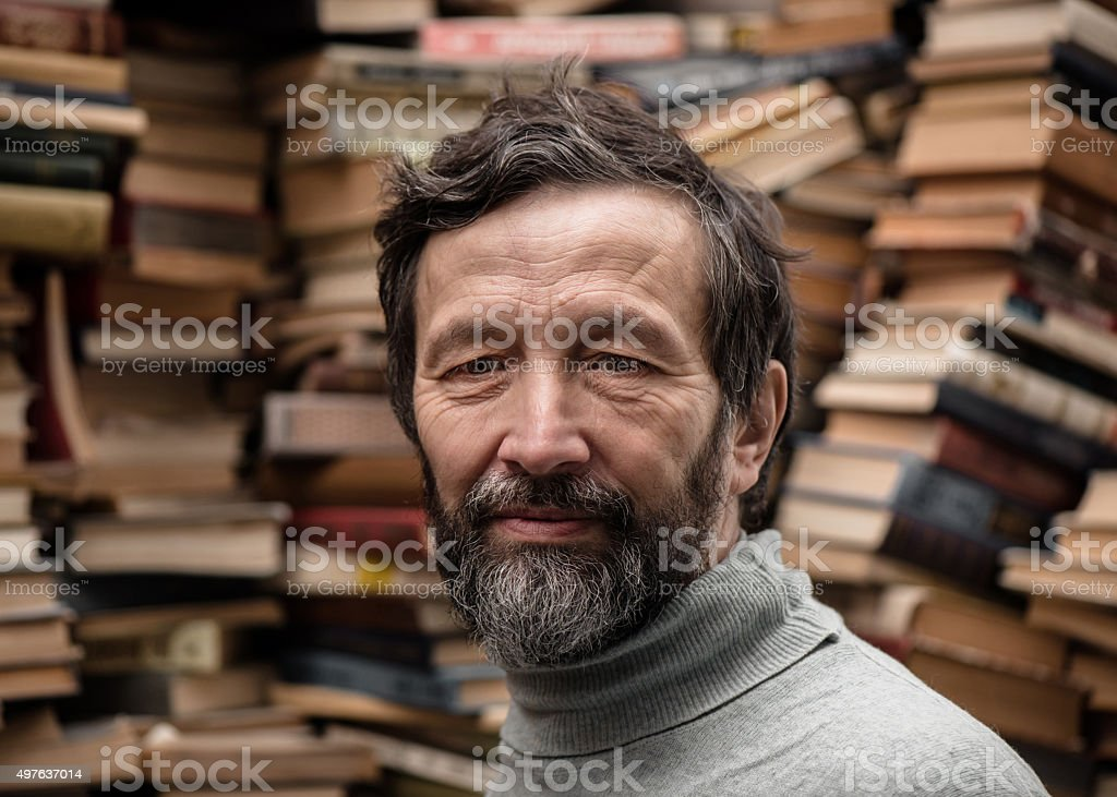 Portrait of senior man with beard on book market stock photo