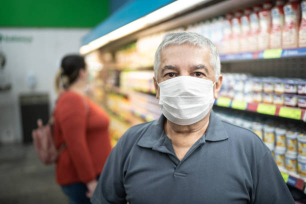Portrait of senior man with face mask shopping in supermarket stock photo