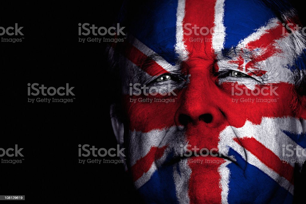 Portrait of Senior Man with Face Painted as British Flag stock photo