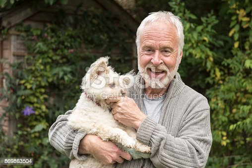 Man in his 60s looking at camera with cheerful expression and stroking pet white dog