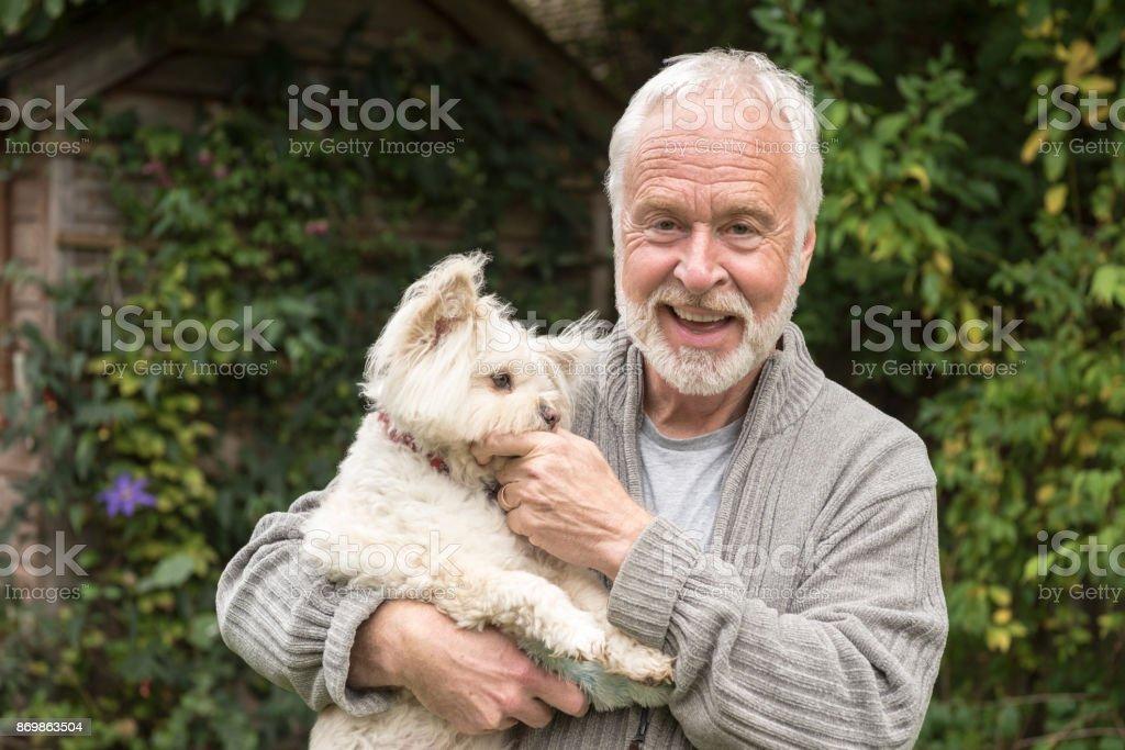 Portrait d'un homme senior avec les cheveux blancs et barbe holding chien - Photo