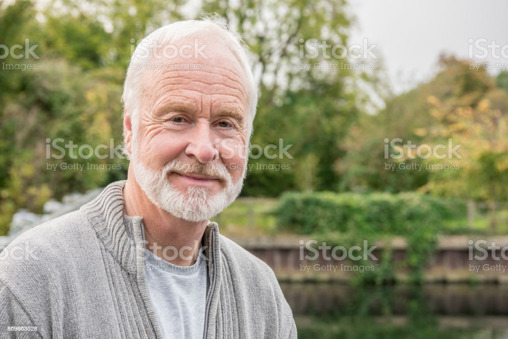 Portrait of senior man with white hair and beard smiling stock photo