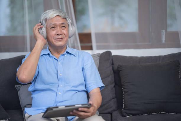 Retrato de hombre mayor, hombre de edad avanzada escuchando música a través de auriculares inalámbricos, concepto de estilo de vida más antiguo. - foto de stock