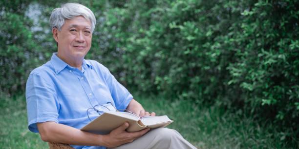 Retrato de hombre mayor, hombre mayor mirando a la cámara después de leer el libro, concepto de estilo de vida antiguo. Fondo del banner con espacio de copia - foto de stock