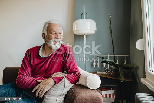 Senior men in a red sweater sitting in a living room at home and looking at window