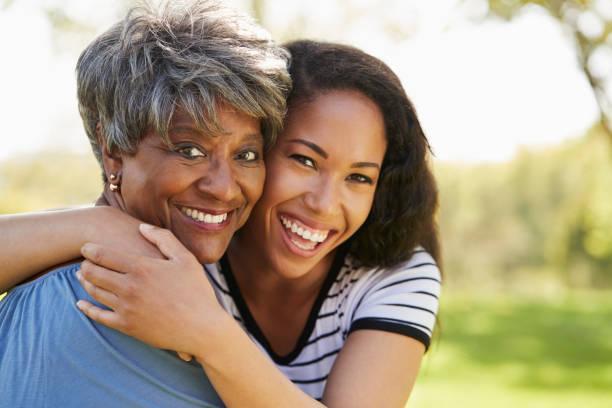 retrato de la madre con hija adulta en parque senior - hija fotografías e imágenes de stock
