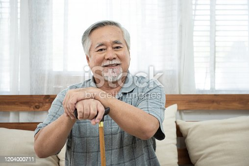 Portrait of senior old elderly asian man sit on coach hand hold help walking stick sit on sofa in house look at camera with happiness and healthy lifestyle.