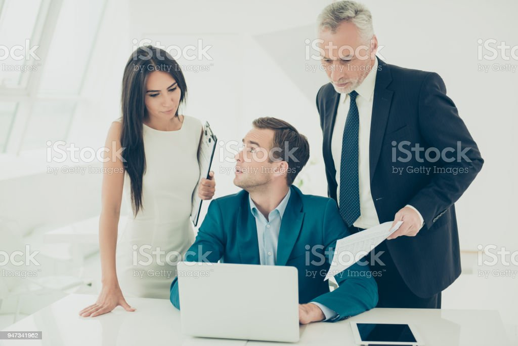 Portrait of senior partners in formal wear helping young manager in...