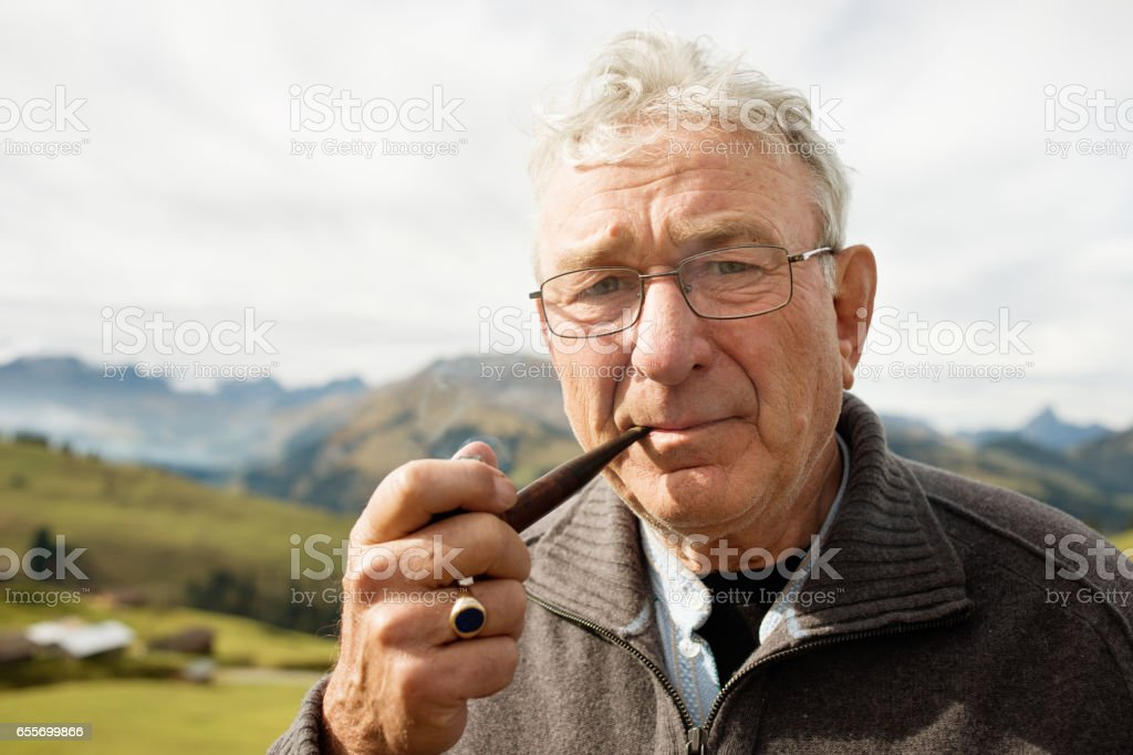 Portrait of Senior Pipe Smoker in the Mountains stock photo