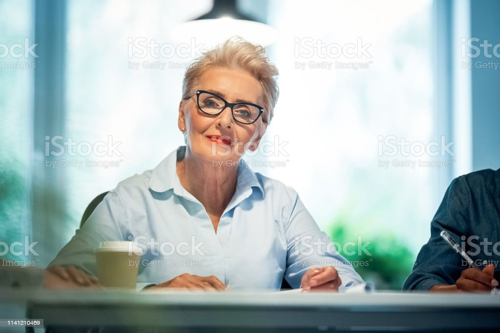 Portrait of senior professional working in office Portrait of confident senior businesswoman working in office. Female expertise is wearing eyeglasses and shirt. She is working on start-up business. 70-79 Years Stock Photo