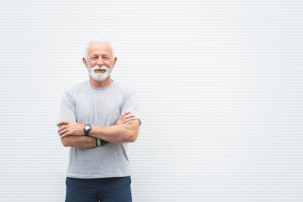 Portrait of senior sportsman standing with arms crossed stock photo