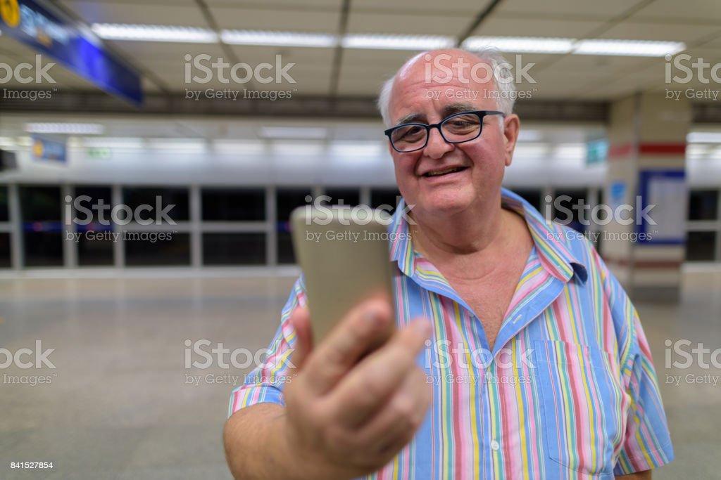 Portrait of senior tourist man inside the MRT subway train station of...