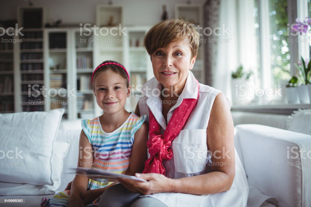 Portrait of senior woman and her granddaughter holding a photo album stock photo