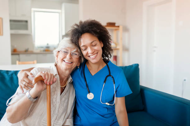 Portrait of Senior Woman and Her Mixed Race Female Caregiver Portrait of Smiling Senior Woman and Her Mixed Race Female Caregiver Together at Nursing Home. Caring Female Doctor Taking Care of a Happy, Elderly Woman nurses stock pictures, royalty-free photos & images